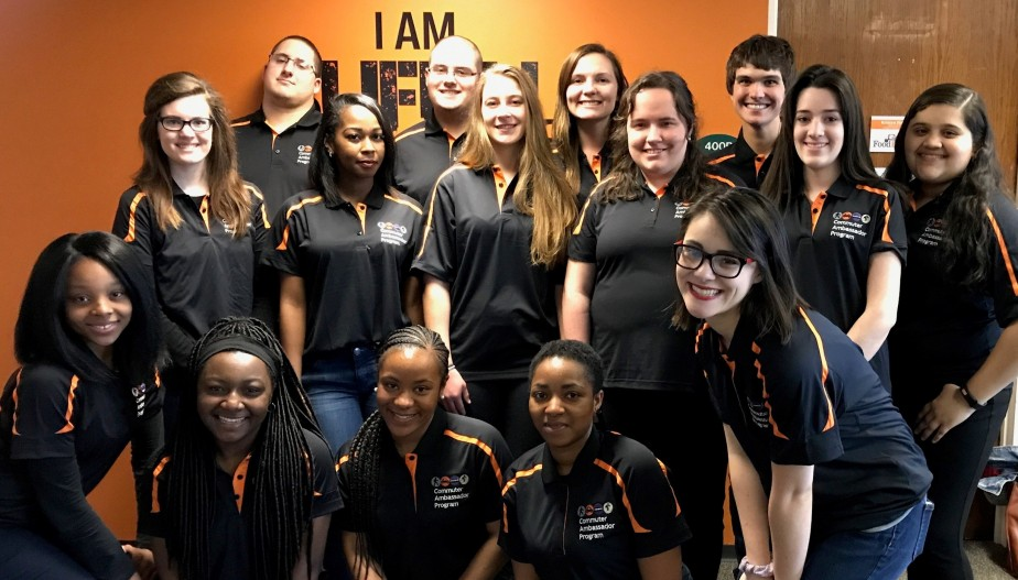 a group of 18 2018 Commuter Ambassadors posing for a picture in their black polo uniforms