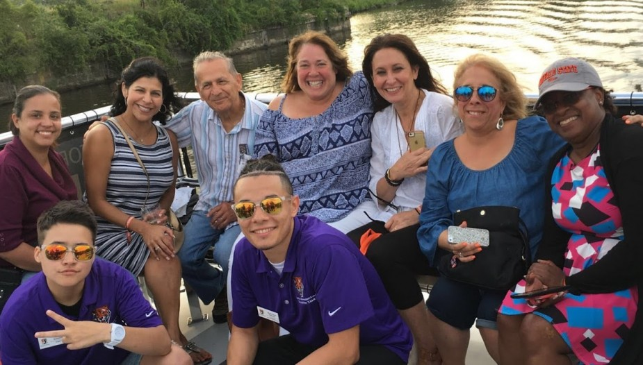 a group of parents posing on a boat with their orientation leader. They are having an excellent time.