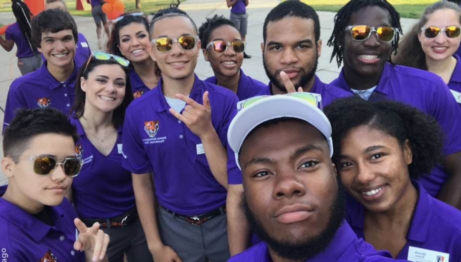 A group of students in purple polos posing for a photo